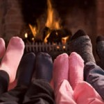 feet in front of fireplace logs